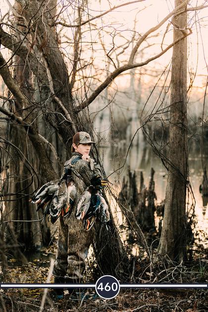 louisiana duck hunting senior boy in cypress trees at sunset wearing waders